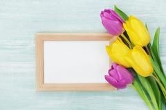 在土气桌上的空的框架和郁金香花为3月8日,国际妇女天,生日或母亲节 库存照片