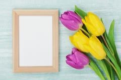 在土气桌上的空的框架和郁金香花为3月8日,国际妇女天,生日或母亲节 图库摄影