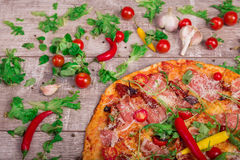在土气桌背景的热的熏火腿薄饼 与菜和意大利辣味香肠的整个意大利薄饼 carpaccio烹调非常好的食物意大利生活方式豪华 免版税库存照片