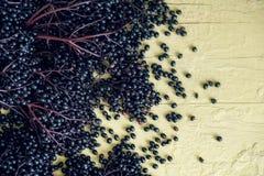 在土气灰色黄色桌上的新鲜的成熟紫罗兰色黑接骨木浆果 免版税图库摄影