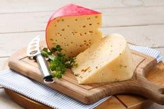 荷兰扁圆形干酪和在盛肉盘的乳酪刀子 免版税库存照片