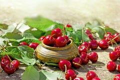 在土气碗的有机樱桃-刷新和水多的莓果 免版税图库摄影