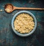 在土气碗的煮熟的奎奴亚藜种子有在黑暗的葡萄酒背景,顶视图的木烹调匙子的 免版税库存图片