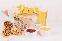 在土气篮子和工艺纸锥体的金黄五颜六色的在碗,在白色木桌上的储藏啤酒的快餐和调味汁 免版税库存图片