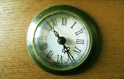 在土气绿色黄色神色的老经典时钟在一张木桌上 免版税库存图片
