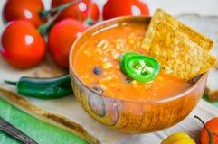 在土气背景的热和辣新鲜的做的墨西哥辣椒汤 免版税库存照片