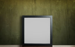 在土气脏的绿色墙壁上的空白的黑框架 免版税库存照片