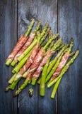 在土气蓝色木背景的熏火腿肉包裹的新鲜的年轻芦笋 免版税库存图片