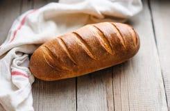 在土气轻的木背景的被烘烤的家制面包 免版税库存图片