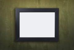 在土气绿色墙壁上的空白的黑框架 库存图片