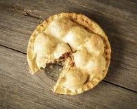 在土气Barnwood的金黄苹果饼与去的一个切片 免版税库存图片