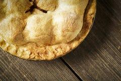 在土气Barnwood的金黄苹果饼 免版税库存照片