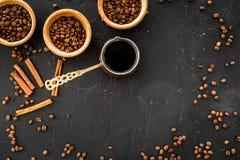 在土耳其咖啡罐的酿造咖啡 黑背景顶视图copyspace 图库摄影