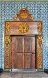 在土耳其陶瓷砖墙壁上的金黄华丽木制框架门框的闭合的木被刻记的年迈的有花卉蓝色样式的 免版税库存照片