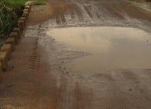 在土路的一个泥泞的水坑 库存图片