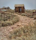在土路的木小屋 免版税图库摄影