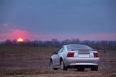 在土路的汽车逗留在日落 免版税库存照片