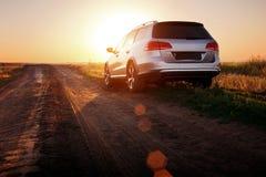 在土路的灰色汽车逗留在日落 免版税库存照片