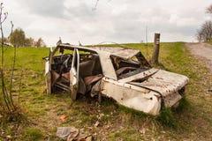 在土路的击毁汽车 被拆卸的车 一个多云春日 图库摄影