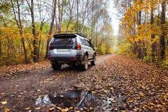 在土路的SUV在秋天森林里 库存照片
