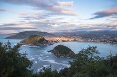 在圣・萨巴斯蒂安海岸线的美好的上部鸟瞰图从山在五颜六色的日落天空的monte igueldo 免版税库存照片