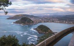 在圣・萨巴斯蒂安海岸线的美好的上部鸟瞰图从山在五颜六色的日落天空的monte igueldo 免版税库存图片