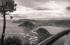 在圣・萨巴斯蒂安海岸线的美好的上部鸟瞰图从山在日落天空的monte igueldo在黑白乌贼属 免版税库存图片
