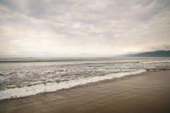 在圣塔蒙尼卡的海浪在多云11月天靠岸 图库摄影
