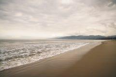在圣塔蒙尼卡的海浪在多云11月天靠岸 免版税库存图片