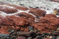 在圣新娘的海滩的红色岩石 免版税库存照片