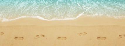 在圣的足迹鞋子 在海滩的海浪 库存照片