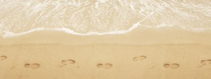 在圣的足迹鞋子 在海滩的海浪 免版税图库摄影
