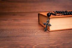在圣经的念珠在木桌上 图库摄影