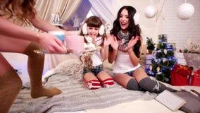 在圣诞前夕,在温暖的舒适大气的快乐的家庭假日的家庭党,妈妈和女儿喝在新的茶 股票视频