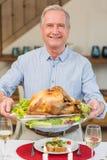 在圣诞晚餐的愉快的成熟人藏品烘烤火鸡 免版税库存照片