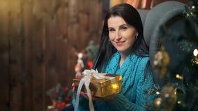 在圣诞树光的微笑的深色的妇女开头礼物盒  股票录像
