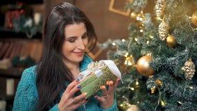 在圣诞树光的微笑的深色的妇女开头礼物盒  股票视频