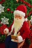 读在圣诞树前面的圣诞老人一本书 免版税库存照片