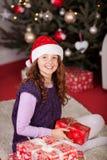 在圣诞树前面的女孩 免版税库存照片