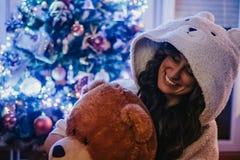 在圣诞树前面的微笑的妇女藏品玩具熊 免版税库存图片