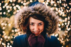在圣诞树前面的愉快的妇女 免版税图库摄影