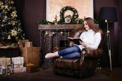 在圣诞树前面的愉快的少妇阅读书 免版税库存图片