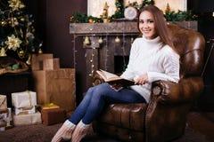 在圣诞树前面的愉快的少妇阅读书 库存图片