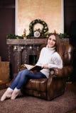 在圣诞树前面的愉快的少妇阅读书 库存照片