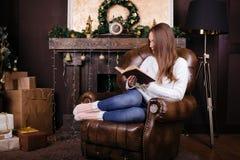 在圣诞树前面的愉快的少妇阅读书 图库摄影