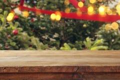 在圣诞树前面的空的桌有装饰背景 对产品显示蒙太奇 免版税库存照片