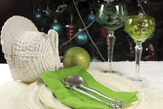 在圣诞树前面的美好的圣诞节桌设置,与绿色水晶酒觚玻璃 免版税图库摄影