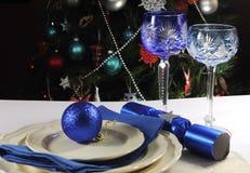 在圣诞树前面的蓝色题材圣诞节桌设置 免版税库存照片
