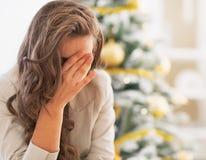 在圣诞树前面的被注重的少妇 免版税库存照片