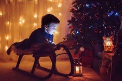 读在圣诞树前面的逗人喜爱的可爱的男孩一本书, 免版税库存照片